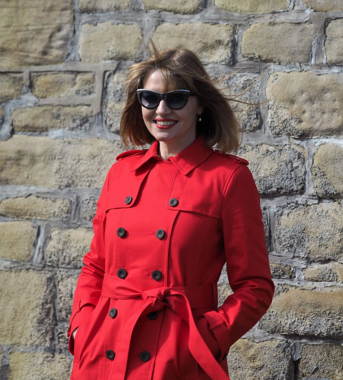 red trench coat jeans outfit and wooden cats eye sunglasses