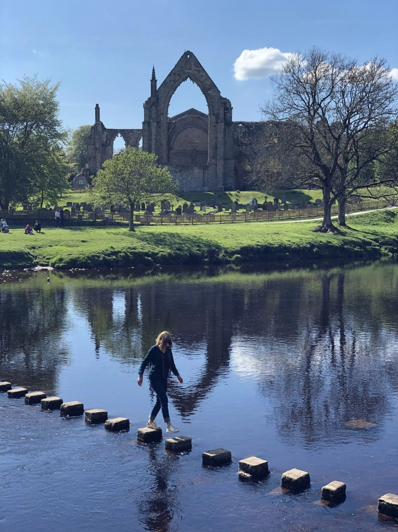 A woman going acrosss stepping stones at Bolton Abbey Blog's sixth birthday