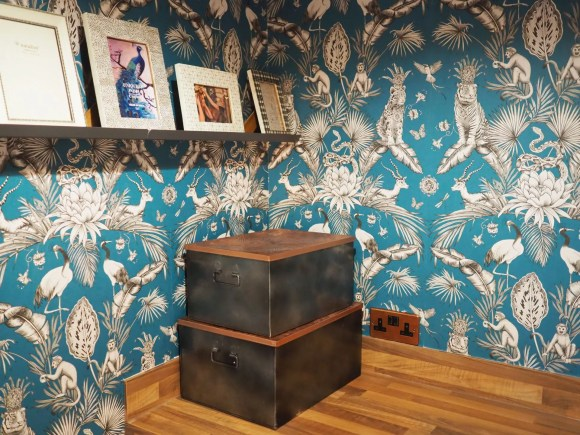 teal menagerie wallpaper and copper accessories