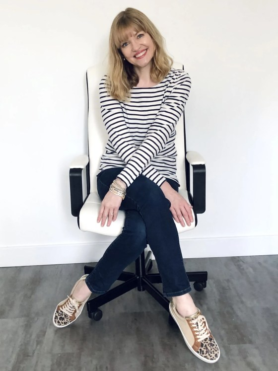 woman sitting in office chair wearing stripey breton top, jeans and leopard print trainers