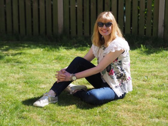 woman wearing lace top and jeans sitting in a garden