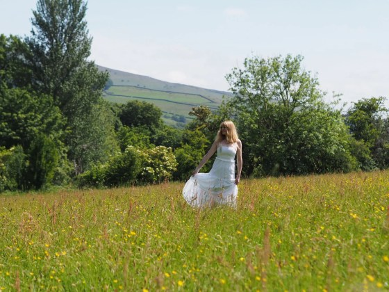 woman in wildflower meadow wearing white broderie anglaise maxi dress and white sunglasses