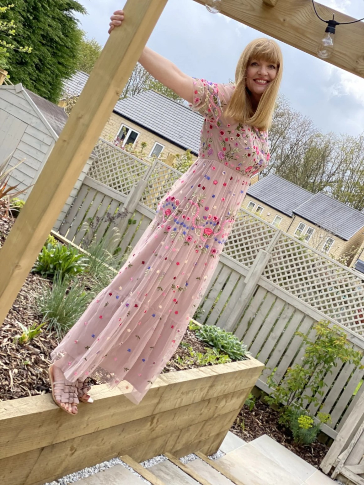 woman wearing blush long dress with all over flowers