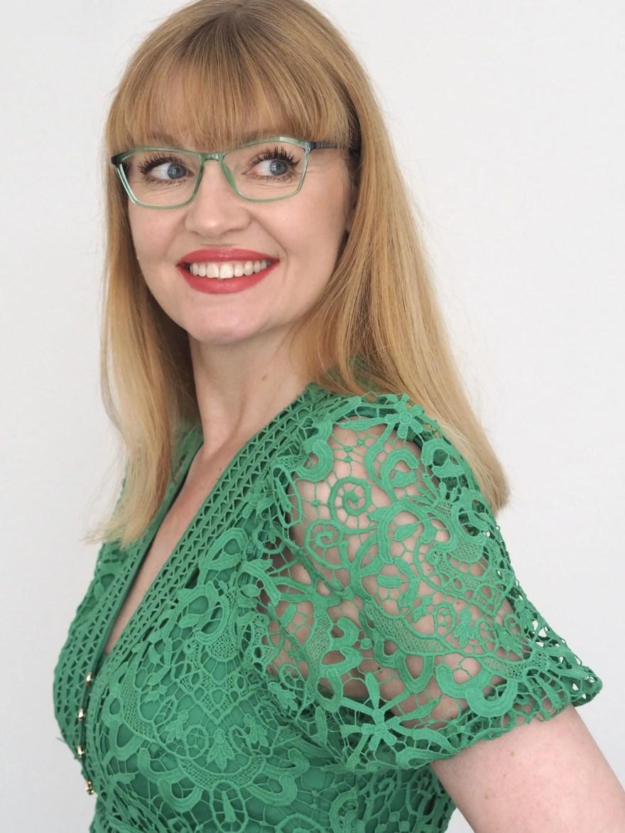 woman wears green dress and matching green eyewear