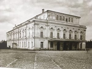 A large white three story building with many windows surrounded by a paved square.