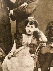 A woman in a white dress, fur stole, and high collar, with an elaborate headpiece in her dark hair sits, with her elbow on the arm of a chaise and her head leaning on her hand, smiling slightly at the camera.