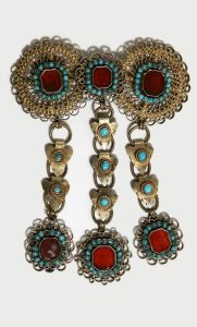 Elaborate silver, ruby and turquoise jewelry, with a large stones on the main body of the piece and dangling links of silver and jewels hanging from below it.