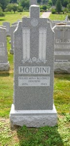 """A tall grey gravestone bears a floral motif and the word """"Houdini"""" in large type, with """"Wilhemina Beatrice Houdini"""" and her birth and death dates beneath."""