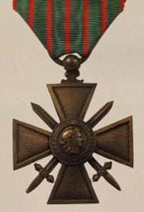 A bronze cross-shaped military decoration, with crossed swords behind the center and a woman's head crowned with laurel leaves