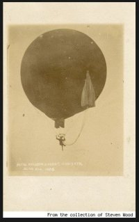 A tintype photo shows a woman dangling on a trapeze below a hot air balloon, her parachute attached to the side of the balloon and by cords to her back. She is not wearing a skirt.