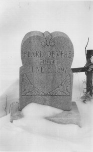 """A grey marble heart-shaped headstone bears the words """"Pearl DeVere died June 5, 1897"""""""