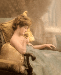 A woman with red hair and a green, low-cut dress reclines in an armchair on gold cushions, eyes closed and sniffing at a golden rose in her hand.