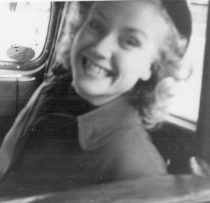 A young woman with a beret, leather coat and black turtleneck smiles radiantly at the camera into the back seat from the front seat of a car