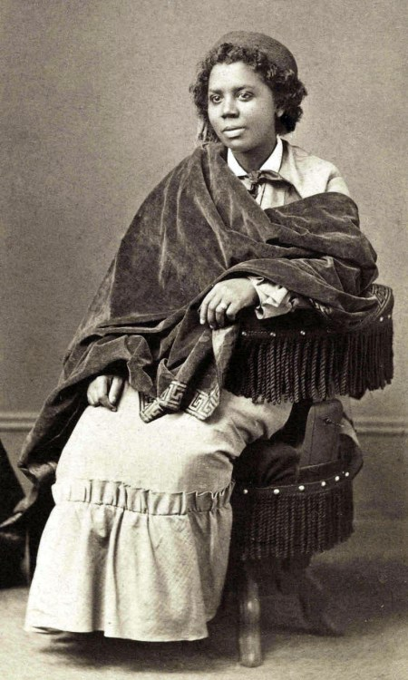 An African-American woman with short hair and wearing a long beige dress, dark-colored velvet shawl and dark fez sits in a fringed circular chair.