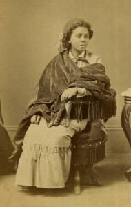 An African-American woman with short hair and wearing a long beige dress, dark-colored velvet shawl and dark fez sits in a fringed circular chair