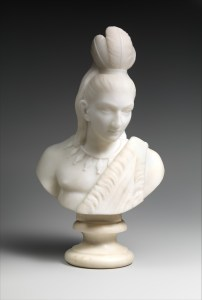 A marble bust in Neo-Classical style of a Native American man with one-shoulder robe, necklace, and top-feather headdress