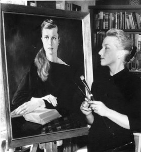A woman holding paintbrushes and wearing all black stands looking at a large portrait on an easel. The portrait depicts a womam with long hair and a black drape sitting at a table with a book.