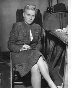 A woman in a fashionable wool skirt suit holds a drawing pad and stares intently at something behind the camera.