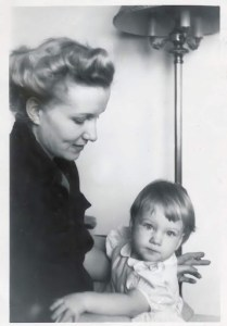 A woman with blonde hair in a 1950s style gazes down at a young toddler girl on her lap. The girl wears a lighg colored dress with Peter-Pan collar and stares into the camera.