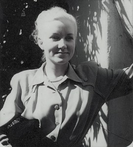 A young woman wearing a fashionable taupe dress leans against a wall and smiles to the right of the camera