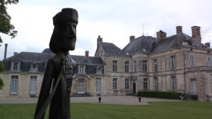 A chateau across a green courtyard with a statue of Voltaire in the foreground