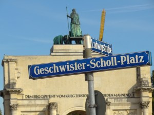"""A street sign reading """"Geschwister-Scholl Platz"""" stand in front of a Univeristy building."""