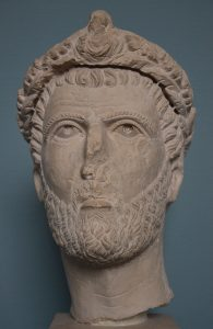 Limestone bust of a bearded man wearing laurel wreath. Face and nose have been damaged.