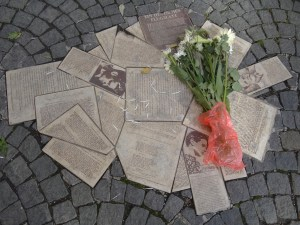 Recreations of some of the flyers created by the White Rose movement on the paving stones near the university where they were left. Someone has left flowers at the site.
