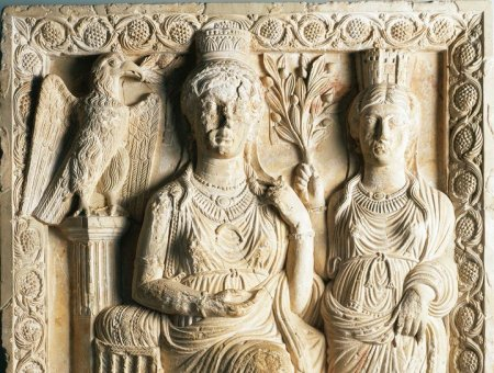 A sculpture in relief of a woman seated on a chair wearing elaborate jewelry and a tall headpiece, with another woman wearing Roman draped robes stands to her left. A bird of prey sits on a pillar to Zenobia's right.