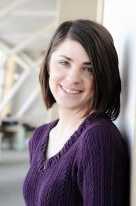 A white woman with shoulder-length dark hair and a purple sweater smiles at the camera over her left shoulder.