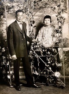 A couple stand in a floral-decorated wire arch