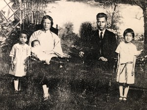 A Chinese American family with two parents and three children sit looking at the camera