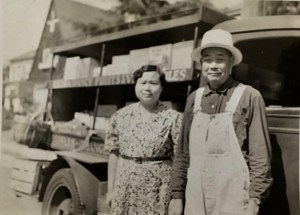 A middle-aged Chinese-American couple stand in front of a large delivery truck full of boxes, smiling at the camera