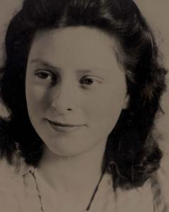 Freddie Oversteegen in 1945. A young girl with dark hair weraing a light blouse smiles, looking off to the left of the viewer