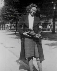 Truus Oversteegen, girl wearing a knee-length skirt and overcoat, smiles at the viewer while holding a military weapon