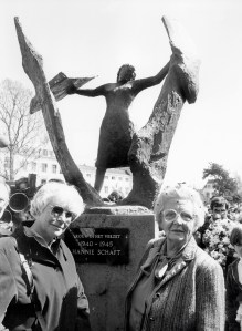 Two women stand in front of a sculpture of a woman standing with arms extended, as if breaking through the walls surrounding her