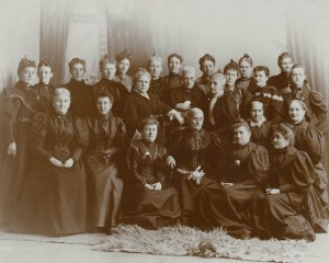 A group of women, all wearing black high-necked gowns, surround Susan B. Anthony