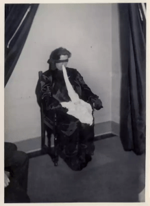 Helen Duncan sits on a chair wearing a blindfold. She has a piece of white something hanging out of her mouth.