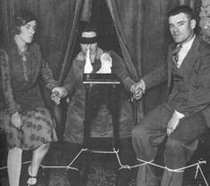 Helen Duncan sits on a chair, with her legs tied to the legs of the people seated beside her, and wearing a blindfold. She has a piece of white something hanging out of her mouth.