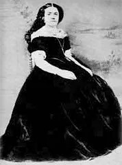 An antique photograph of Eilley Bowers, a white woman wearing a black off-the-shoulder victorian-style gown, with dark hair unbound hanging down her back. She sits on a chair and looks at the camera.
