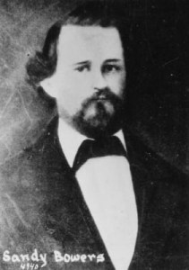 A black and white photo of Eilley Bowers' third husband, Sandy Bowers: a white man with dark hair and beard, wearing a white shirt, black suit jacket and black western bow tie