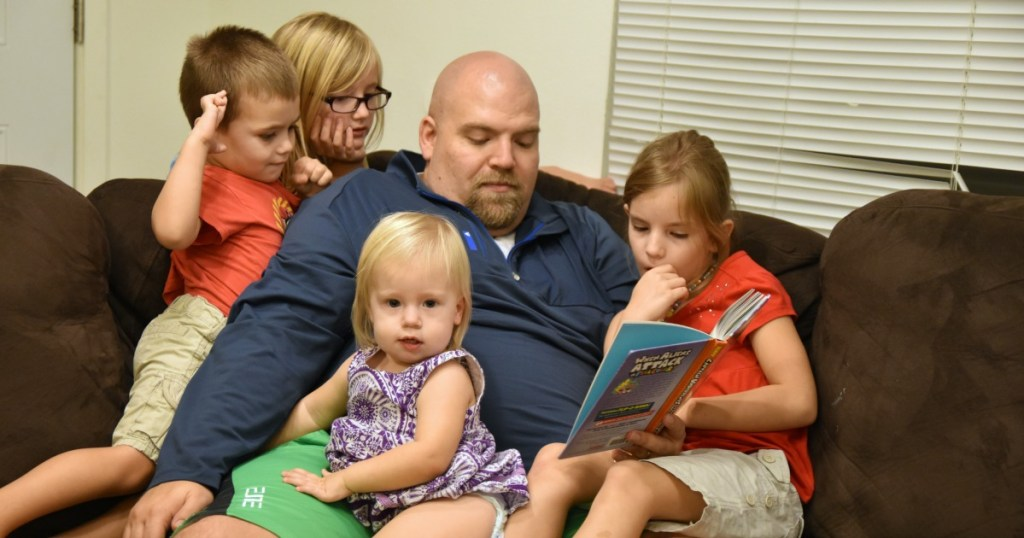 parental involvement ideas include normal things like a father reading to his four children on the couch