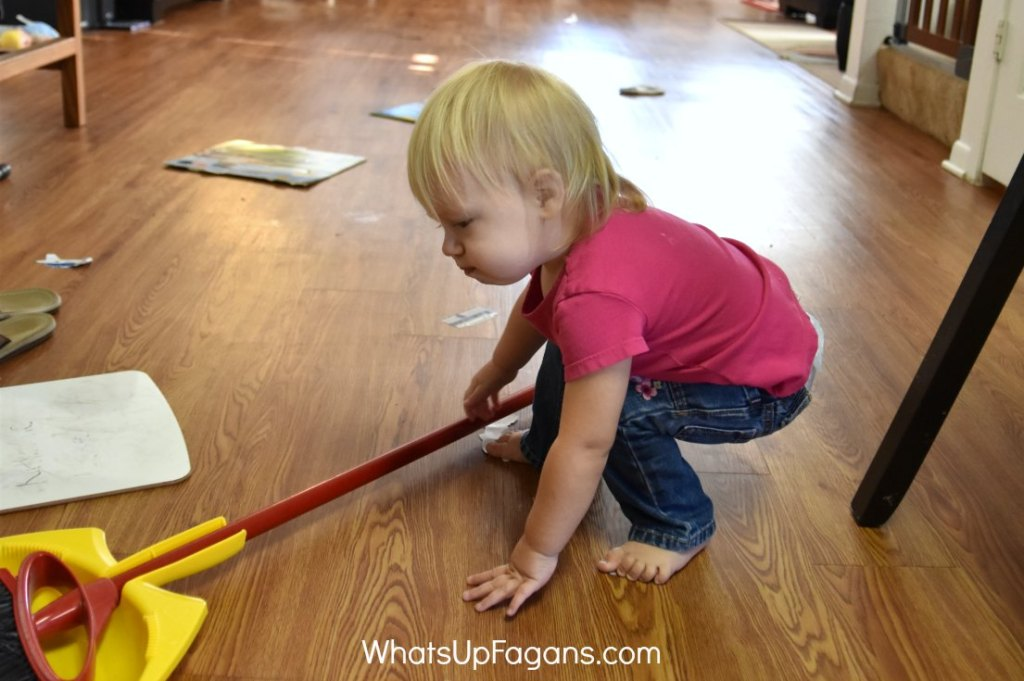 A baby picks up a broom