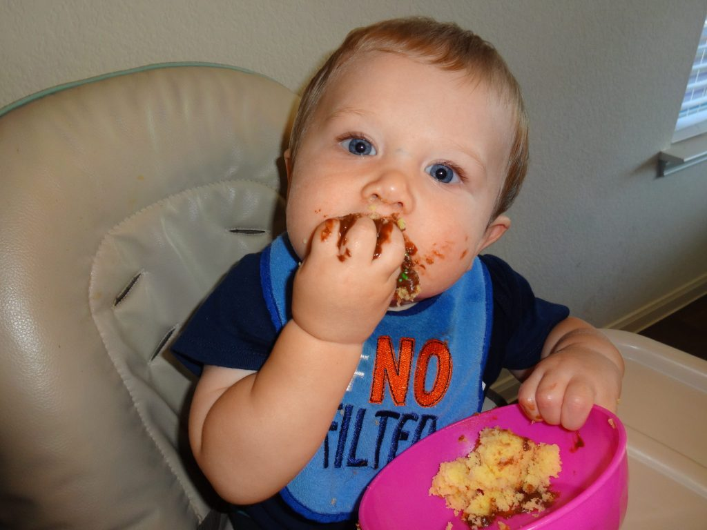 messy baby boy eating food - tips on how to wean to sippy cup