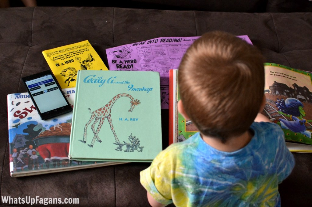 little boy child being encouraged to read books at home thanks to summer reading program from the library