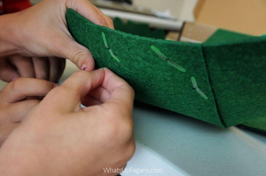 little kid hands assembling a homemade dinosaur costume using brass fasteners