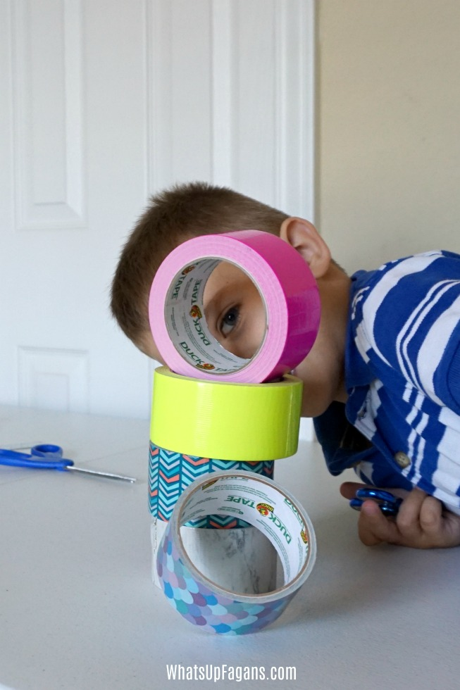 colorful and patterned Duck brand Duct tape and little boy peeking through the hole of one