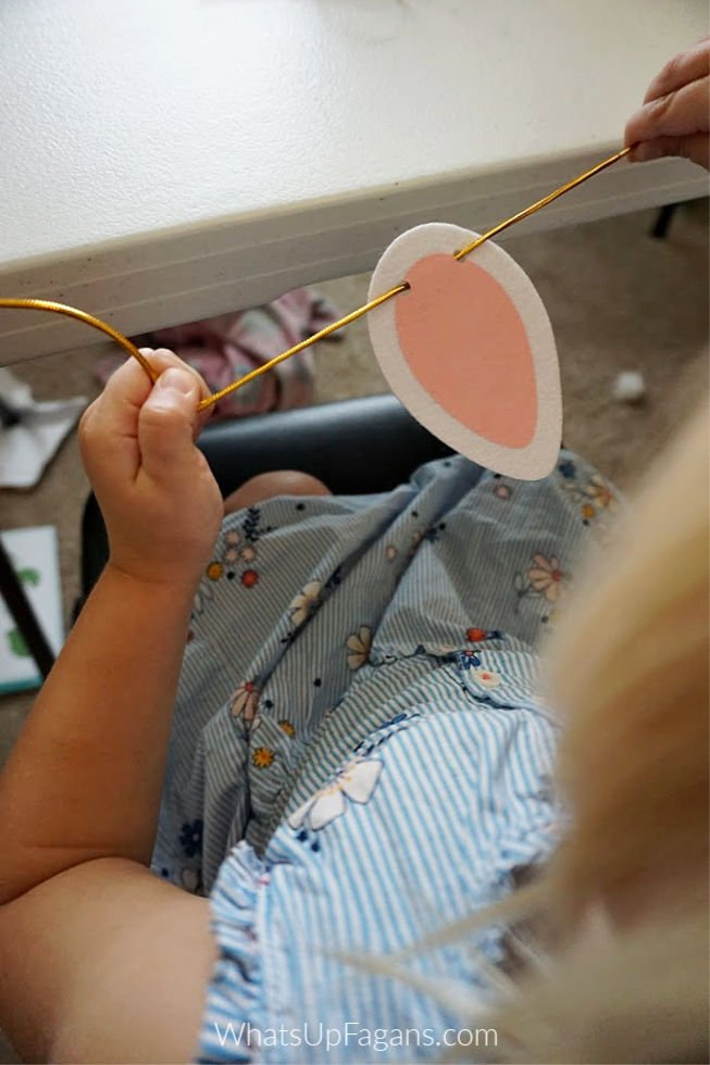 how to make a unicorn costume - little girl trying to make unicorn ears with gold string from Kiwico's DIY unicorn costume kit