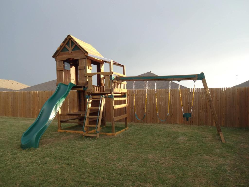 play outdoor backyard games for kids like swinging, sliding, and pretending with a backyard swingset playground playset.