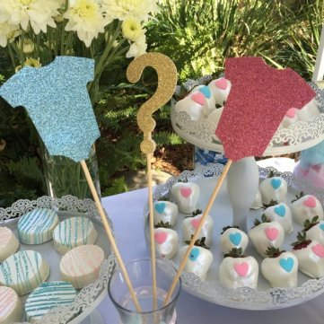 gender reveal party centerpiece ideas using sticks holding a question mark and a onesie cutout in blue and pink